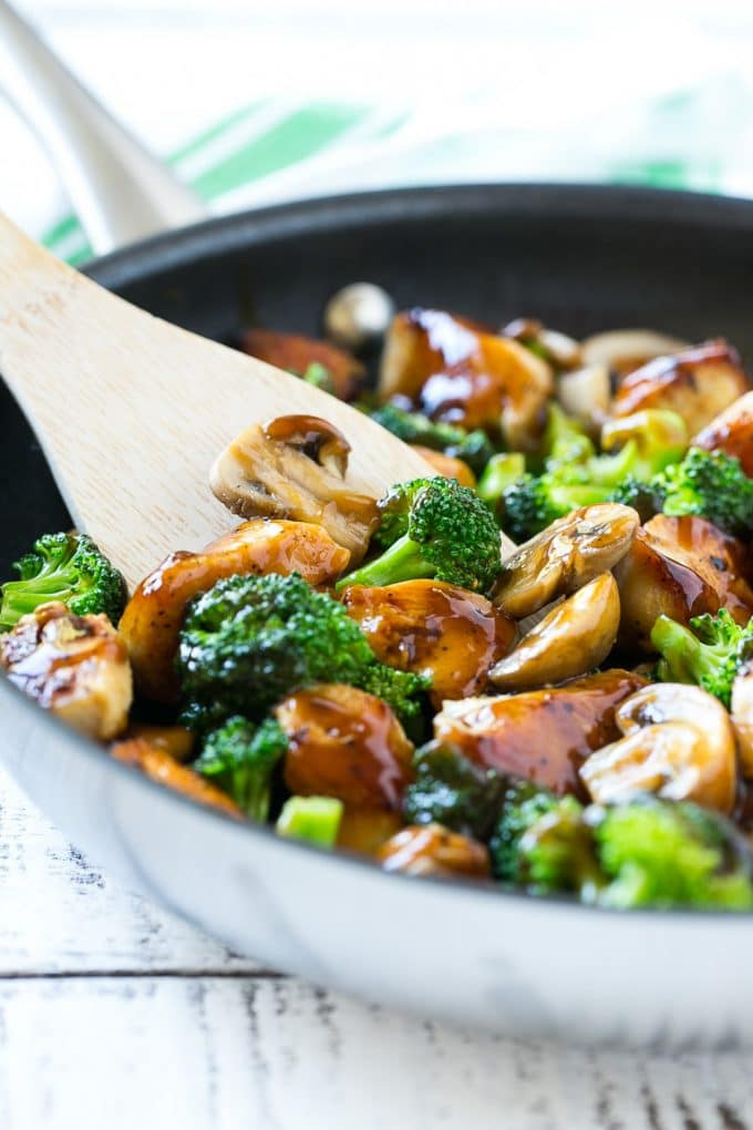 chicken and broccoli stir fry in a large wok on a white wooden board