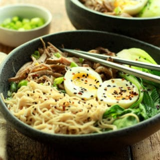 pulled pork ramen in a black bowl topped with a runny egg and chopsticks