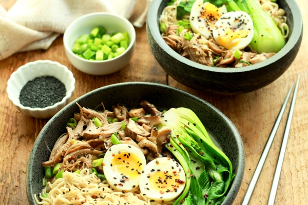 two bowls of pulled pork ramen bowls on a wooden board with chopsticks on the side