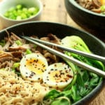 a bowl of pulled pork ramen topped with a runny egg and silver chopsticks