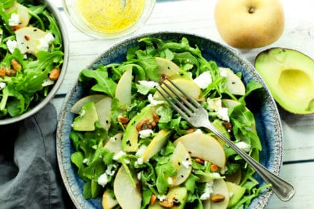 Two bowls of arugula salad topped with Asian pears and avocados with dressing on the side