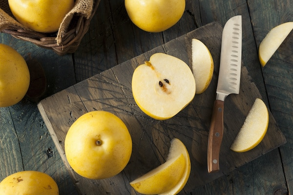 Asian pears on a wooden board with a slicing knife