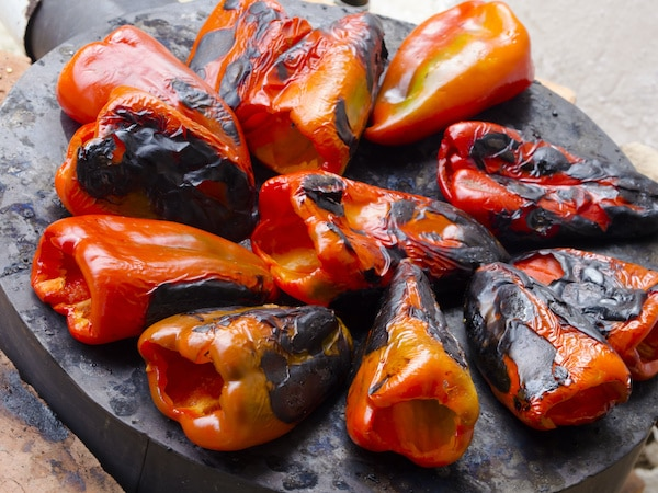 char-grilled mini peppers on a black board