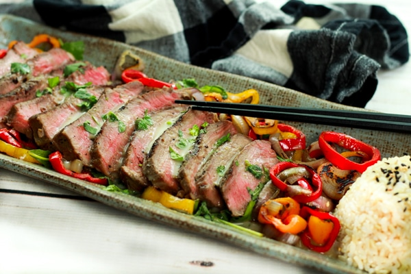 Slices of grilled beef topped with roasted peppers, rice, and chopsticks on the side