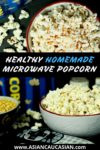 Two heaping bowls of homemade microwave popcorn with spice bottles behind.