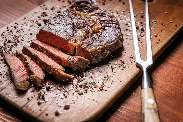 tasty and fresh, very juicy grilled steak sliced on a wooden board