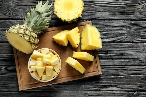 fresh pineapple sliced and chunked on a wooden board