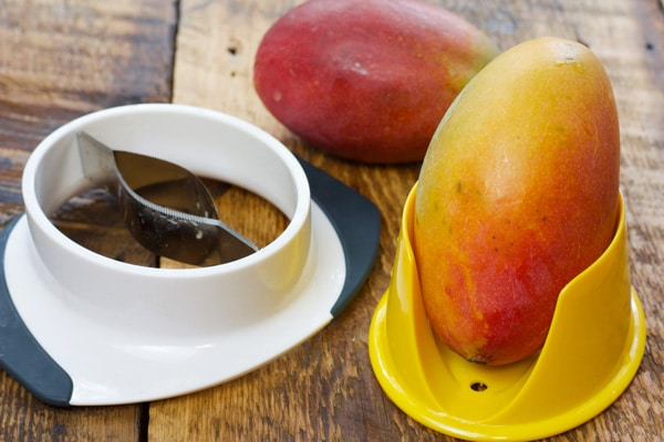 fresh mango in a mango cutter on a wooden board
