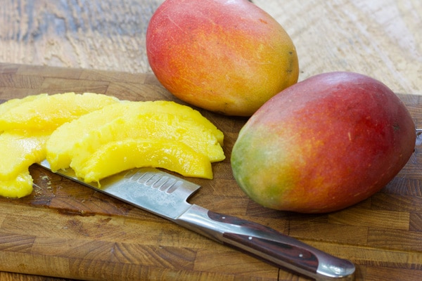 fresh mangos on a wooden cutting board with a knife and slices of mango