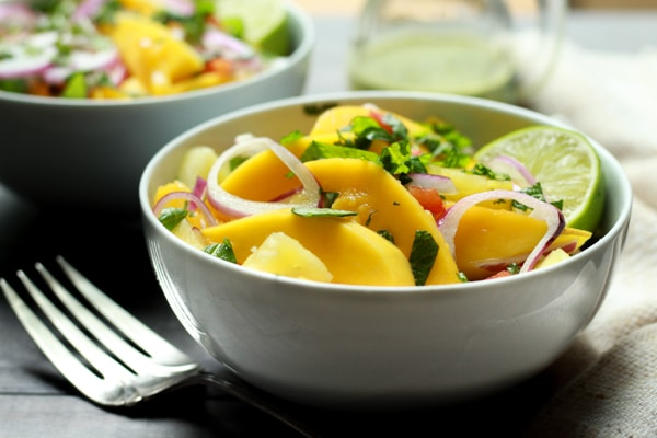 vibrant mango and pineapple salad in white bowls with lime vinaigrette on the side