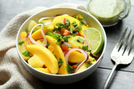 vibrant mango and pineapple salad in white bowls with a silver fork