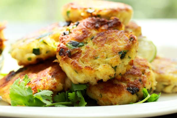 a stack of mini crab cakes on a white plate garnished with fresh cilantro sprigs