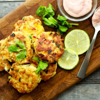 Mini crab cakes stacked on a wooden board with a side of aioli dipping sauce and fresh limes