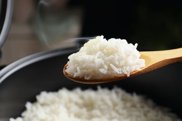 Steamed white rice on a wooden spoon held above a rice cooker