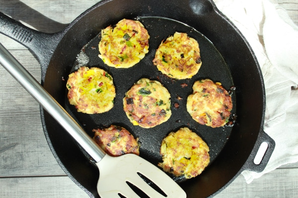 Fried mini crab cakes in a cast iron pan with a spatula on the side