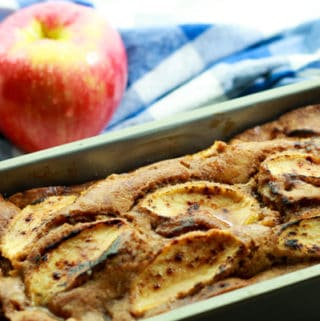 apple ginger bread in a loaf pan with red apples in the background