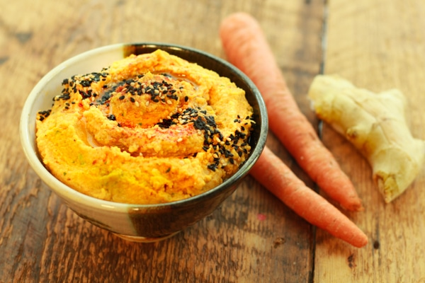 a bowl of roasted carrot and ginger hummus on a wooden board with raw carrots and fresh ginger on the side