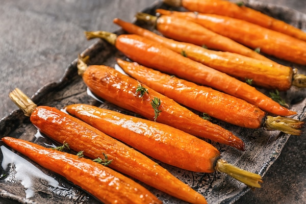A plate of tasty roasted carrots on a table