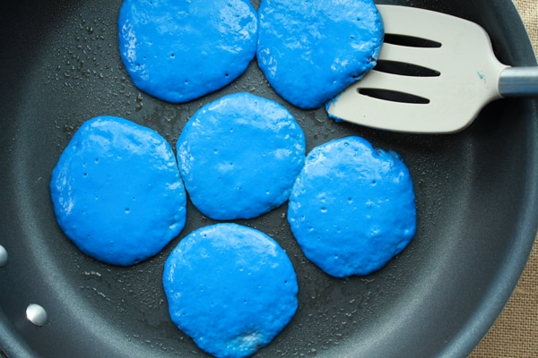 blue pancakes in a frying pan with a spatula