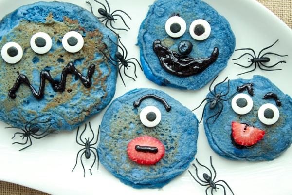 decorated blue monster pancakes on a white plate with black plastic spiders crawling on the plate