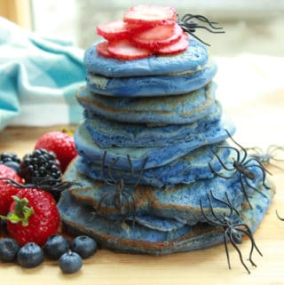 a stack of blue pancakes on a wooden board with vibrant berries on the side and plastic spiders crawling up the stack