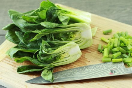 Baby bok choy on a wooden cutting board with a chef's knife and chopped scallions on the side