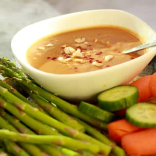 peanut sauce inside a small white bowl surrounded by fresh vegetables