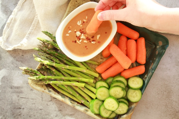 a woman dipping a carrot into a small white bowl of peanut sauce that is placed on a tray with fresh vegetables