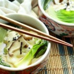 a bowl filled with vibrant wonton soup with chopsticks on a bamboo placemat