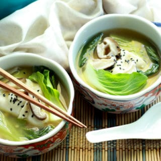 two bowls filled with wonton soup and chopsticks and a white spoon on the side