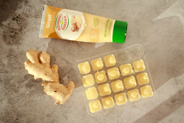 three ginger options on a board including ginger paste, fresh ginger bulb, and frozen ginger cubes