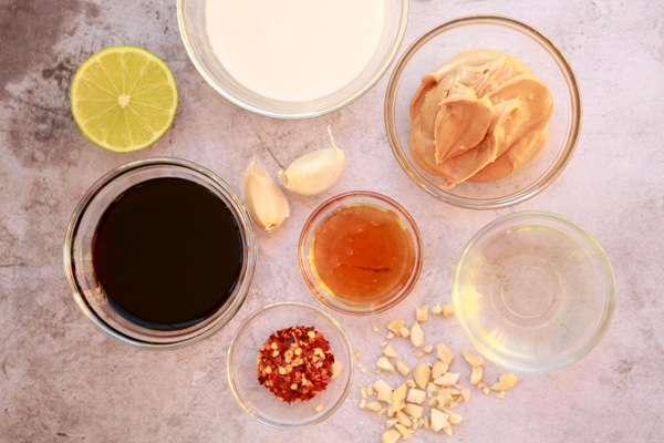 various ingredients for making peanut sauce on top of a gray surface