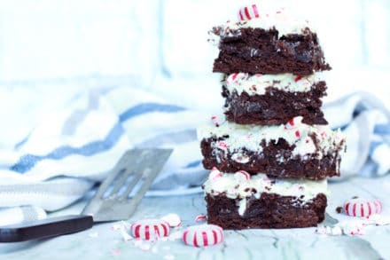 A stack of peppermint brownies on a white surface with peppermint candies along side