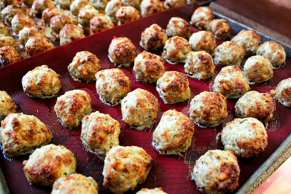 baked meatballs on a red silicon mat on top of a baking sheet