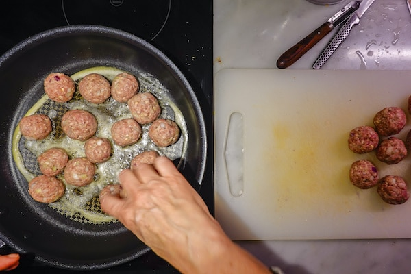 turkey meatballs being fried up in a skillet on the stove
