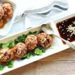 Shrimp and turkey meatballs on a narrow white plate with a side of dipping sauce
