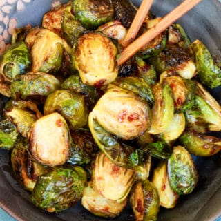 Roasted Brussels sprouts in a blue bowl with chopsticks on top of a wooden board