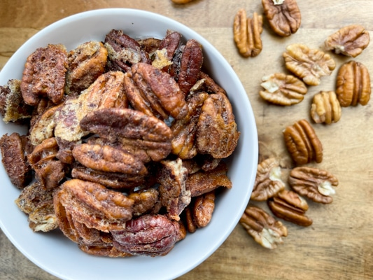 A white bowl filled with golden, spiced pecans and loose raw pecans on the side on a wooden board.