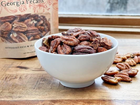 Spiced whole pecans in a white bowl with a bag of pecans and loose pecans on the side on a wooden board.
