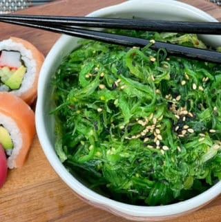 A bowl filled with Japanese seaweed salad with black chopsticks on top and assorted sushi on the side, on a wooden board.