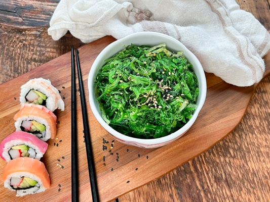 A bowl filled with Japanese seaweed salad with black chopsticks and assorted sushi on the side, on a wooden board with a linen napkin