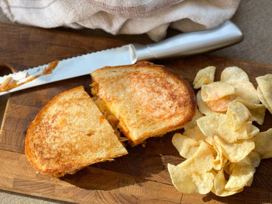 A golden grilled cheese sandwich sliced in half on a wooden board with potato chips and a cutting knife on the side.