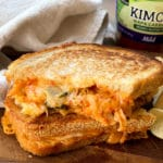 a stacked kimchi grilled cheese sandwich on a wooden board
