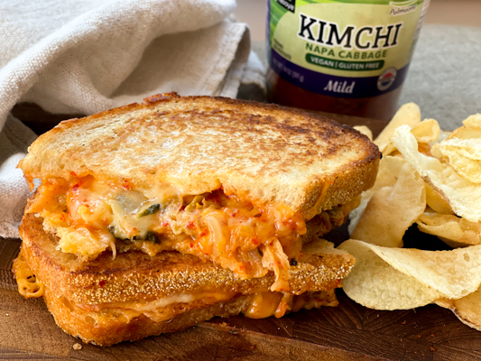 A stacked kimchi grilled cheese sandwich on a wooden board with a jar of kimchi behind it.