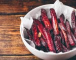 Oven baked beet fries in a white bowl on top of a wooden board