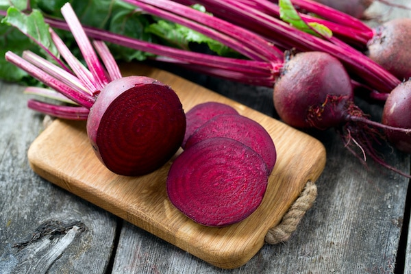 Fresh sliced red beetroot on wooden cutting board with whole red beets behind it.