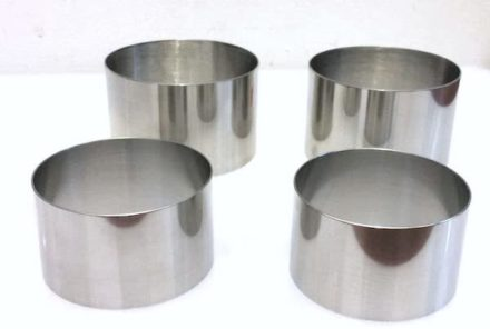 A set of four food stainless steel ring molds on a white board