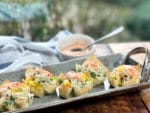 A long gray serving platter with baked wonton cups filled with crab salad and a dollop of colorful aioli on top on a wooden board and a small white bowl of aioli behind it.