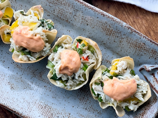 A long gray serving platter with baked wonton cups filled with crab salad and a dollop of aioli on top sitting on top of a wooden board.