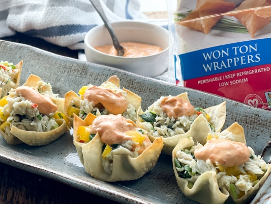 A gray serving platter with wonton cups filled with crab salad and a dollop of aioli on top with the package of wonton wrappers behind it.